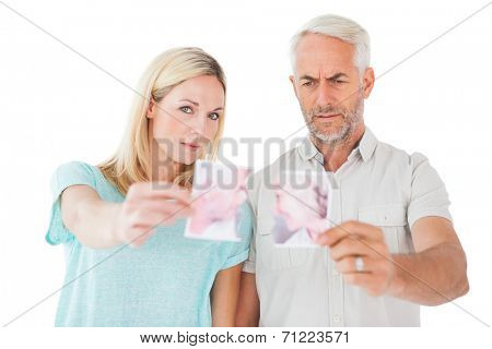 Unhappy couple holding two halves of torn photograph on white background