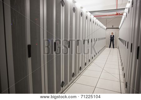 Serious technician standing in server hallway in large data center