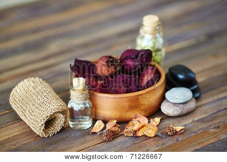 Dry roses, leaves, spa stones and essential oils on wooden surface