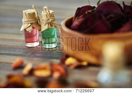 Aromatic essences in small bottles with dry roses near by