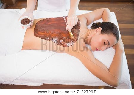 High angle view of an attractive young woman receiving chocolate back mask at spa center