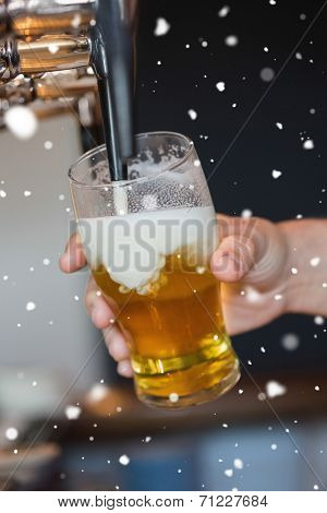 Hand holding glass filling beer against snow falling