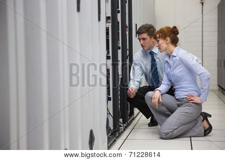 Team of technicians kneeling and looking at servers in large data center