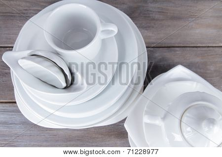White crockery and kitchen utensils, on wooden