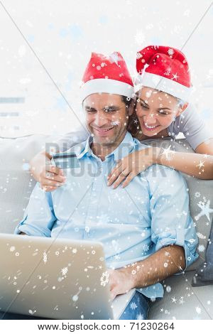 Cute couple in santa hats shopping online with laptop against snow falling
