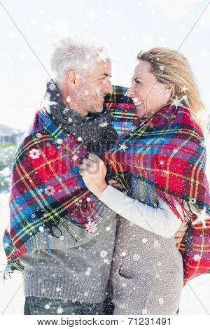 Happy couple wrapped up in blanket standing on the beach against snow falling