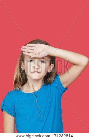 Portrait of sad girl checking self temperature against red background