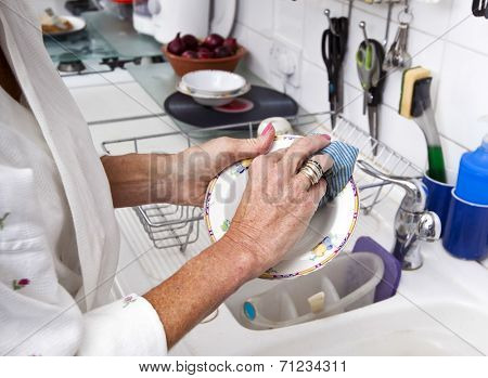 Cropped image of senior woman cleaning plate in kitchen