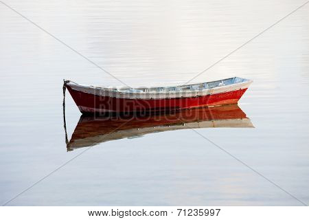 Lone red boat floating on a calm sea
