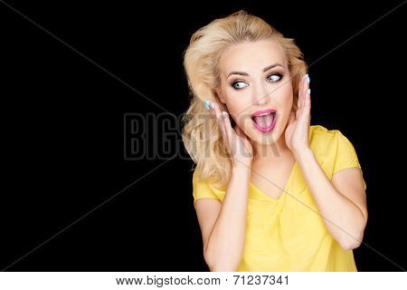 Beautiful young woman reacting in amazement holding her hands to her blond hair with her mouth open in awe  on black with copyspace
