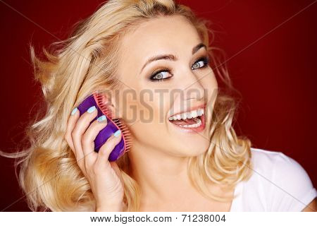 Vivacious blond woman brushing her hair as she looks sideways at the camera with a playful laugh