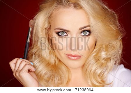 Beautiful blond woman with a quirky expression looking directly at the camera as she holds a cosmetics makeup brush in her hand