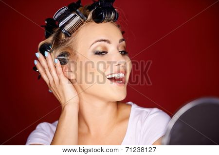 Beautiful young woman with her blond hair in curlers primping in front of a mirror laughing and flirting with herself in a narcissistic way