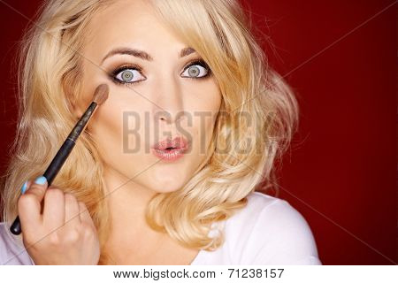 Beautiful sexy woman pouting seductively at the camera as she applies blusher with a large soft cosmetics brush