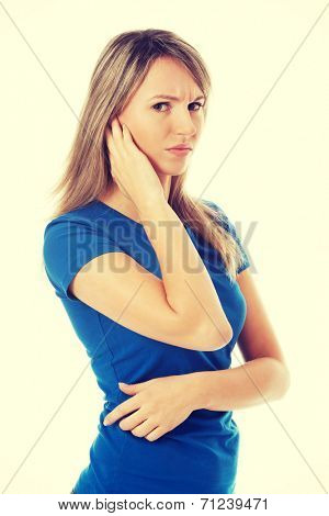 Young casual woman touching her ear. Isolated on white.