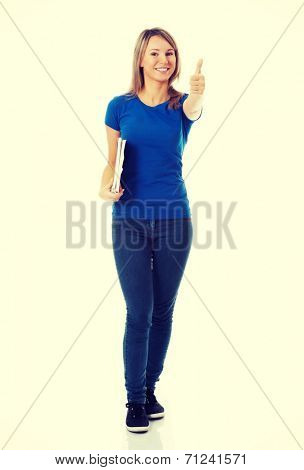 Young beautiful student woman showing OK, holding workbook. Isolated on white.