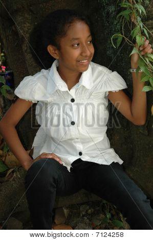 little girl sit down beside the tree