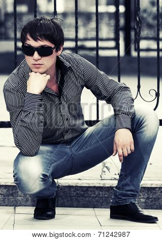 Young handsome fashion man sitting at the cast iron fence