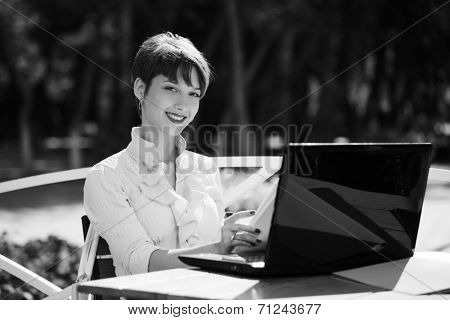 Happy young business woman using laptop at sidewalk cafe