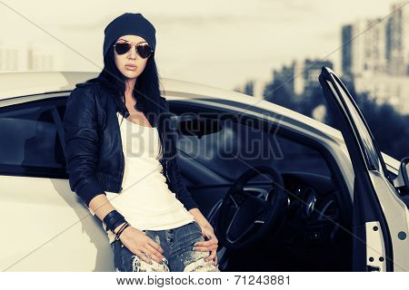 Fashion punk woman in sunglasses standing at the car