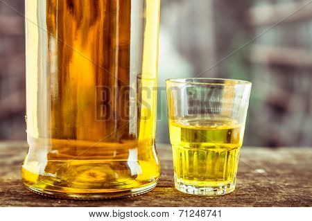 Bottle and glass shot with yellow liqour resembling whiskey, rum, tequila, spirit