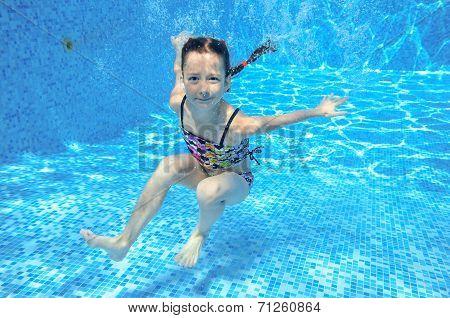 Happy active underwater kid swims in pool