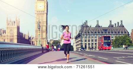 London lifestyle woman running near Big Ben. Female runner jogging training in city with red double decker bus. Fitness girl smiling happy on Westminster Bridge, London, England, United Kingdom.
