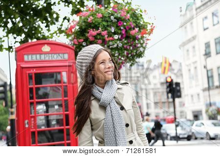 People in London- woman by red phone booth. Portrait of beautiful smiling happy young female casual professional business woman walking outside in City of Westminster, London, England, Great Britain.
