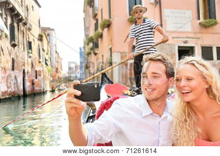 Travel couple in Venice on Gondole ride romance in boat happy on vacation holidays. Romantic young beautiful couple taking selfie photo with smartphone sailing in venetian canal in gondola. Italy.
