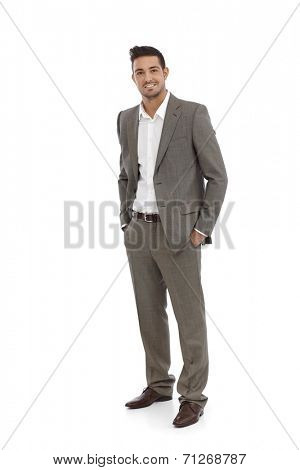 Handsome businessman standing in grey suit, hands in pocket.