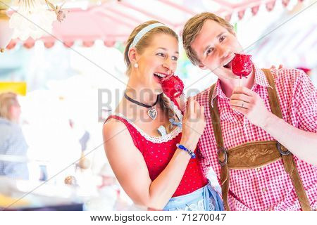 Couple visiting together Bavarian fair in national costume eating  candy apple