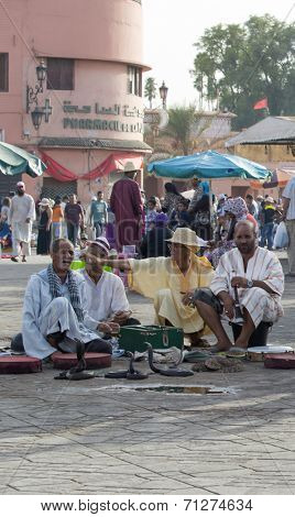 MARRAKESH, MAROCCO - AUGUST 24: Snake charmers in the Djemaa el Fna - market place in Marrakesh's medina quarter on 24 August 2014 in Marrakesh, Morocco. Djemaa el Fna is a UNESCO world heritage site.