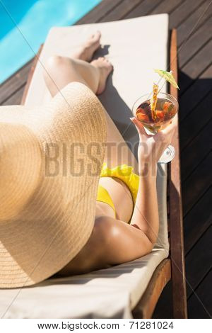 High angle view of beautiful young woman holding drink by swimming pool