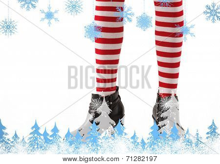 Lower half of girl wearing stripey socks and boots against snowflakes and fir trees