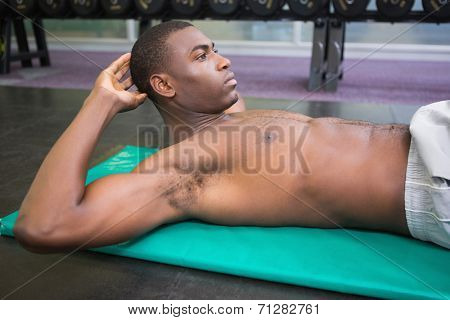 Side view of a shirtless muscular man doing abdominal crunches in gym