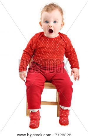 Shocked and startled baby girl dressed in red looking at camera isolated on white