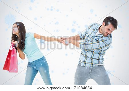 Attractive young man pulling his shopaholic girlfriend against snow falling