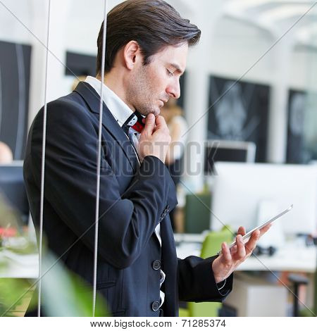 Pensive man in office looking at tablet computer in the office