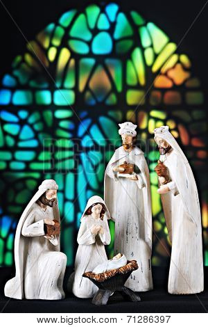 A nativity scene composed of the 3 magi, Mary and the baby Jesus set before a stained glass window.