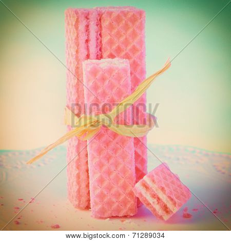 Pink wafer sugar cookies tied with raffia with an instagram look. Square format with a retro vignette.