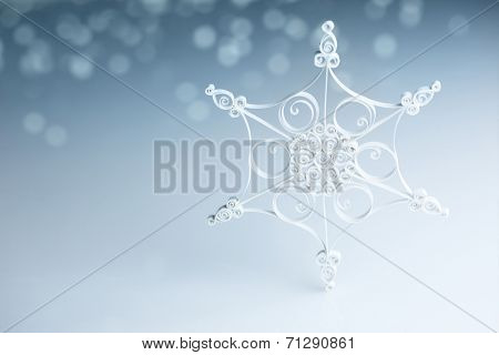 Beautiful handmade paper curved snowflake on blue white background with bokeh - horizontal