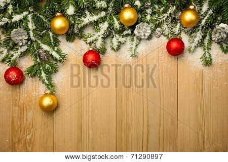 Christmas background with fresh firtree and  baubles on wood with bright snow
