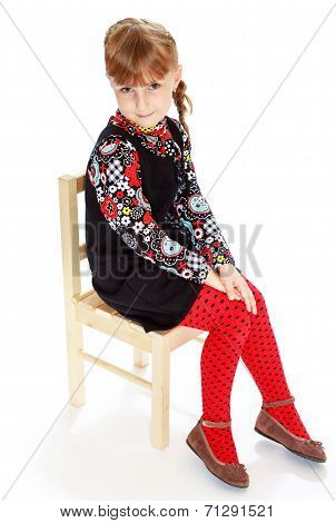 girl sitting on a chair with her hands