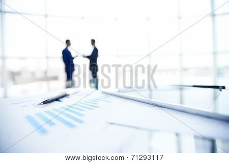 Business documents and pen at workplace on background of businessmen interacting