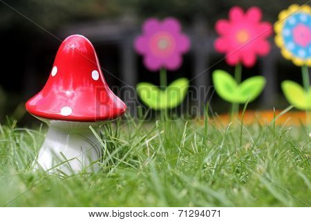 Big Red Mushroom Toy With Colorful Artificial Flowers In Background