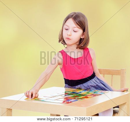 Girl schoolgirl sits at a table