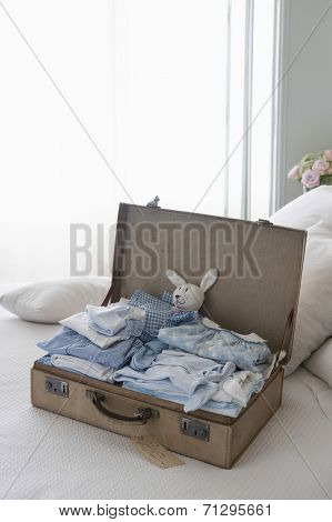 Ironed and folded children's clothing in open suitcase on bed