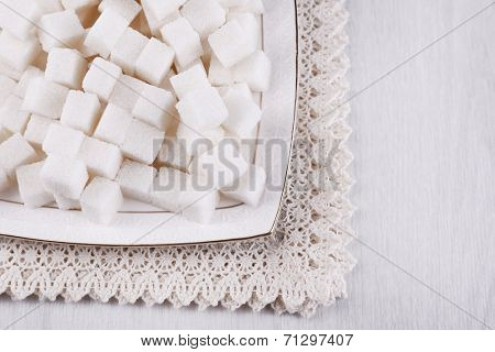 Refined sugar on plate on wooden background
