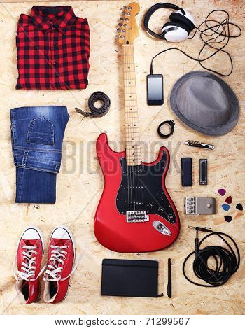 Musical equipment, clothes and footwear on wooden background
