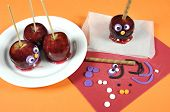 picture of toffee  - Decorating red toffee apples with funny crazy smiling faces for Halloween trick or treat food candy on an orange table setting - JPG